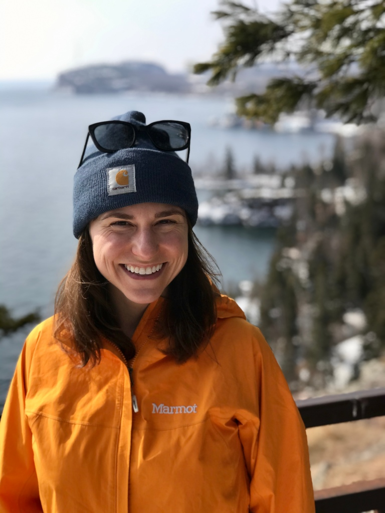 Color headshot of Emily P.G. Erickson at a lookout at Tettegouche State Park, Minnesota. Emily P.G. Erickson is wearing a bright orange coat, blue hat, and is smiling right at the camera. Behind her are white pines dotted with snow and gray Lake Superior.