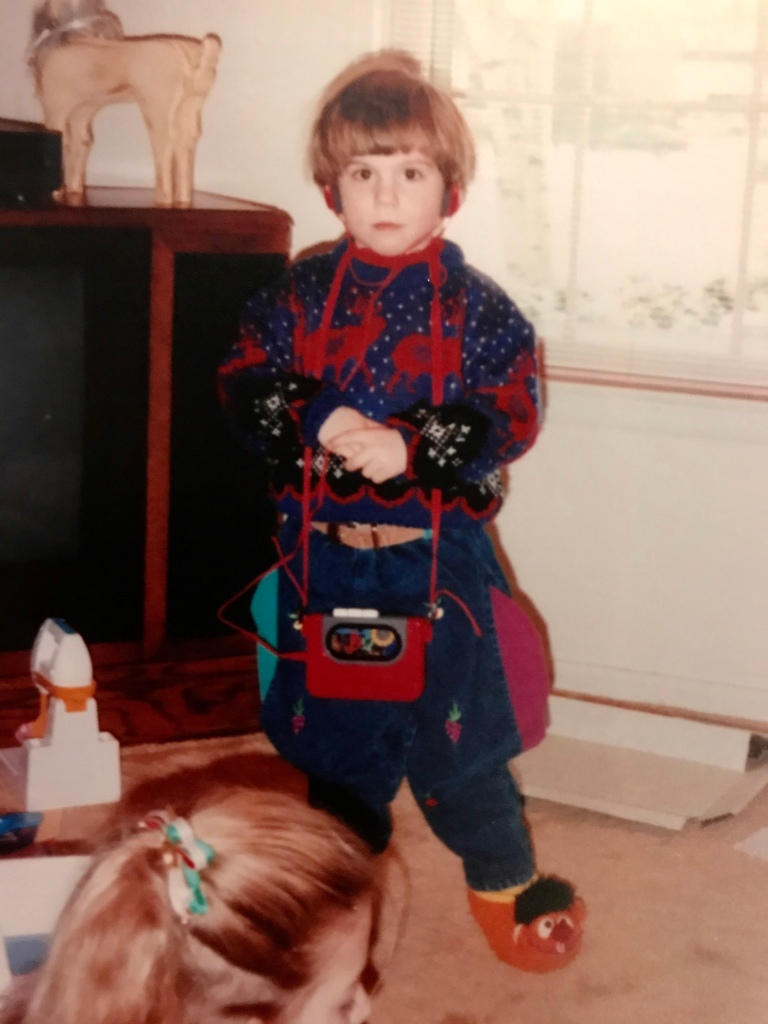 An old photograph of Emily P.G. Erickson, maybe age 3 or 4. She has a bowl cut and is standing with her hands clasped. She has on a red and blue reindeer sweater and has a red walkman on her neck. She is wearing Earnie slippers on her feet.