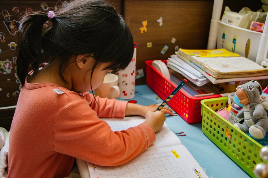 Young kindergartener doing a workbook at home during the pandemic
